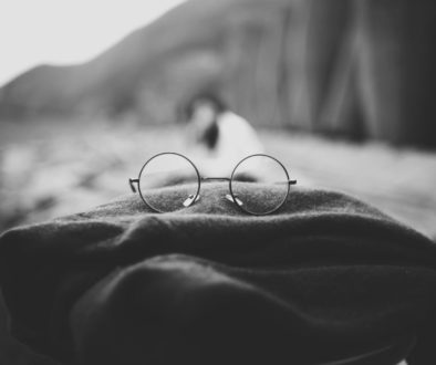 Grayscale photo of round glasses placed on top of a folded scarf with a figure and some cliffs blurred in the background, perhaps on a beach.