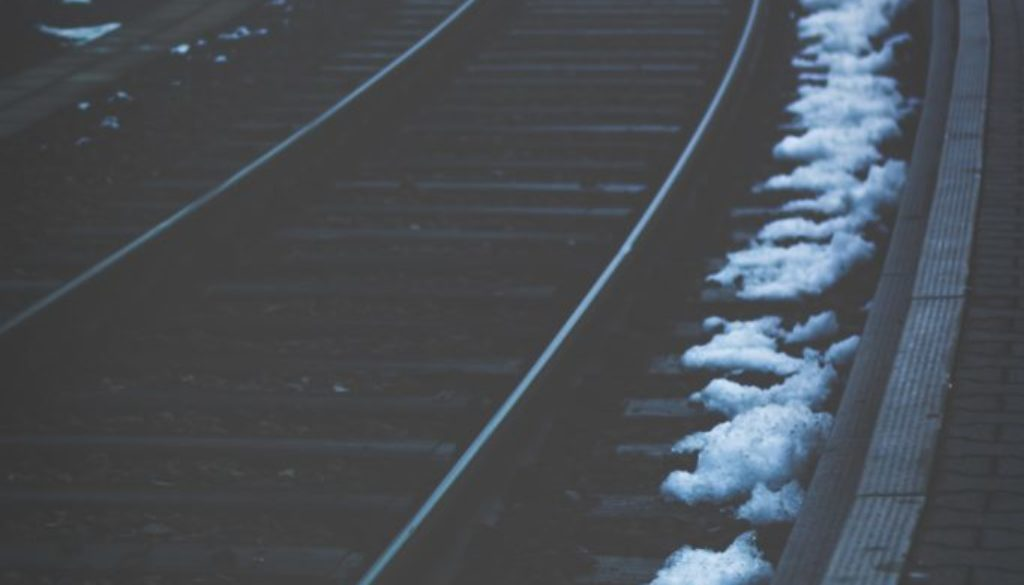 Empty train track lined with snow